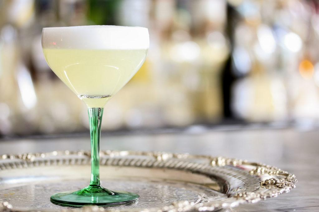 a lemon cocktail placed in the centre of an antique silver tray