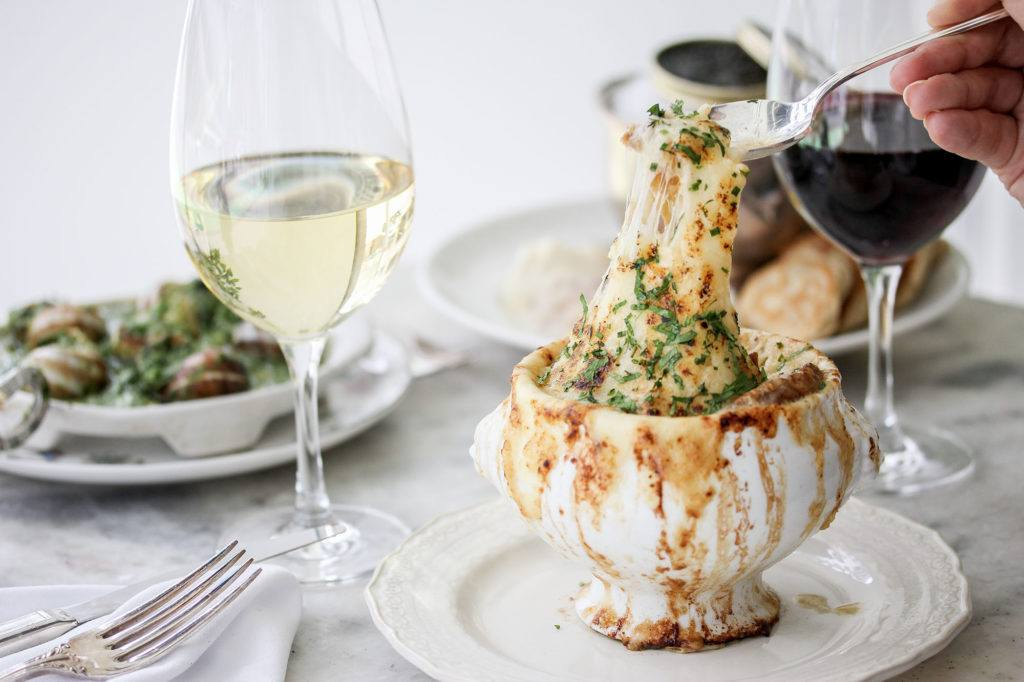 Bowl of French onion soup on a white plate with a spoon