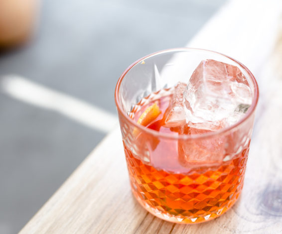 Classic negroni cocktail served in a rocks glass on a wooden table outside.