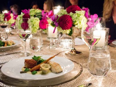 a dinner plate with beautifully plated food served on a table with place-settings, centrepieces and wine glasses