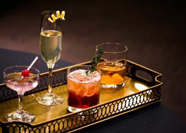 a gold serving tray with four different types of fancy cocktails at The Carlu in Toronto