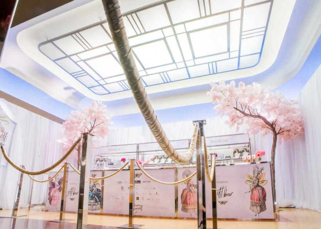 a luxurious event showcase counter display with dream like decor and soft pink flowers