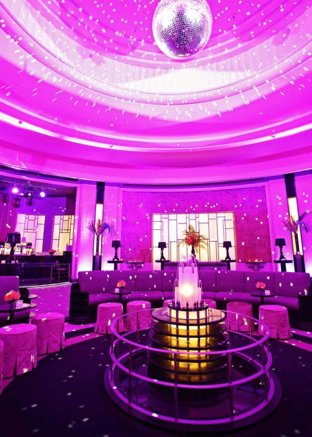 a circular large couch under a glimmering disco ball with dim, purple lights filling the Round Room at The Carlu