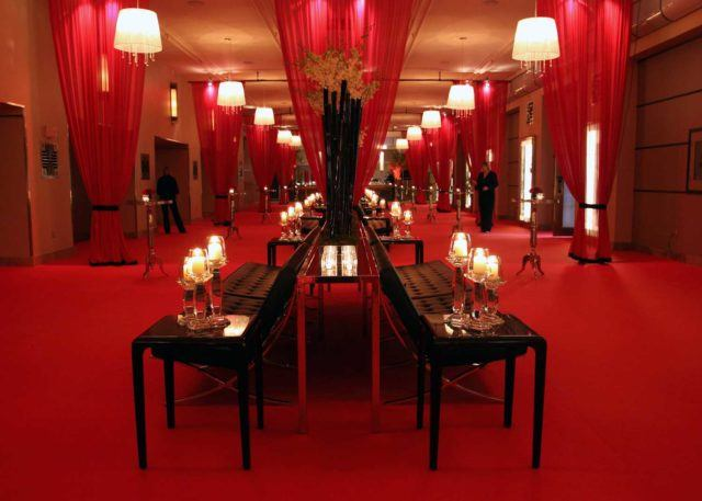 a long elegant hallway in deep red decor, red carpets, red tables and long benches