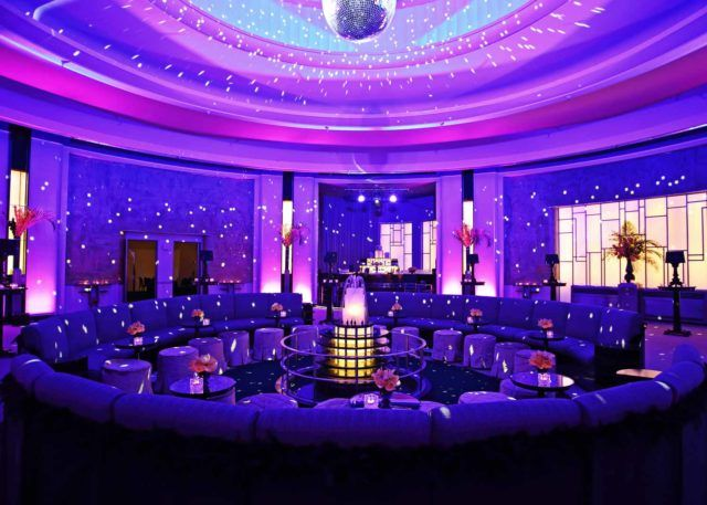 a circular large couch under a glimmering disco ball in the Round Room at The Carlu, a Toronto event venue
