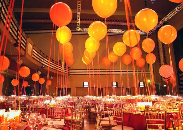 The Concert Hall at The Carlu filled with circular tables and chairs for dining guests under a ceiling full of floating balloons