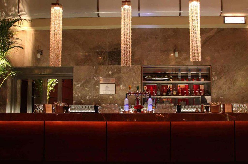 The bar at The Carlu Toronto with deep red tones, marbled stone walls, and long crystal-strung hanging lights