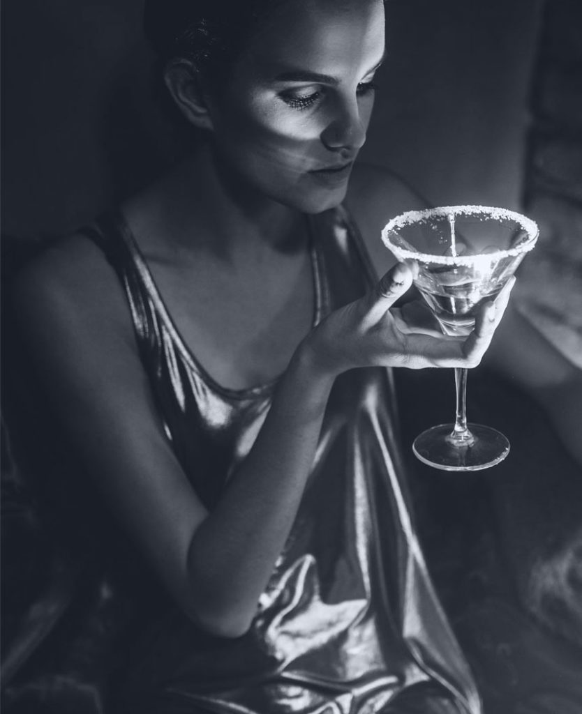 a woman in a shiny dress holding a cocktail glass.