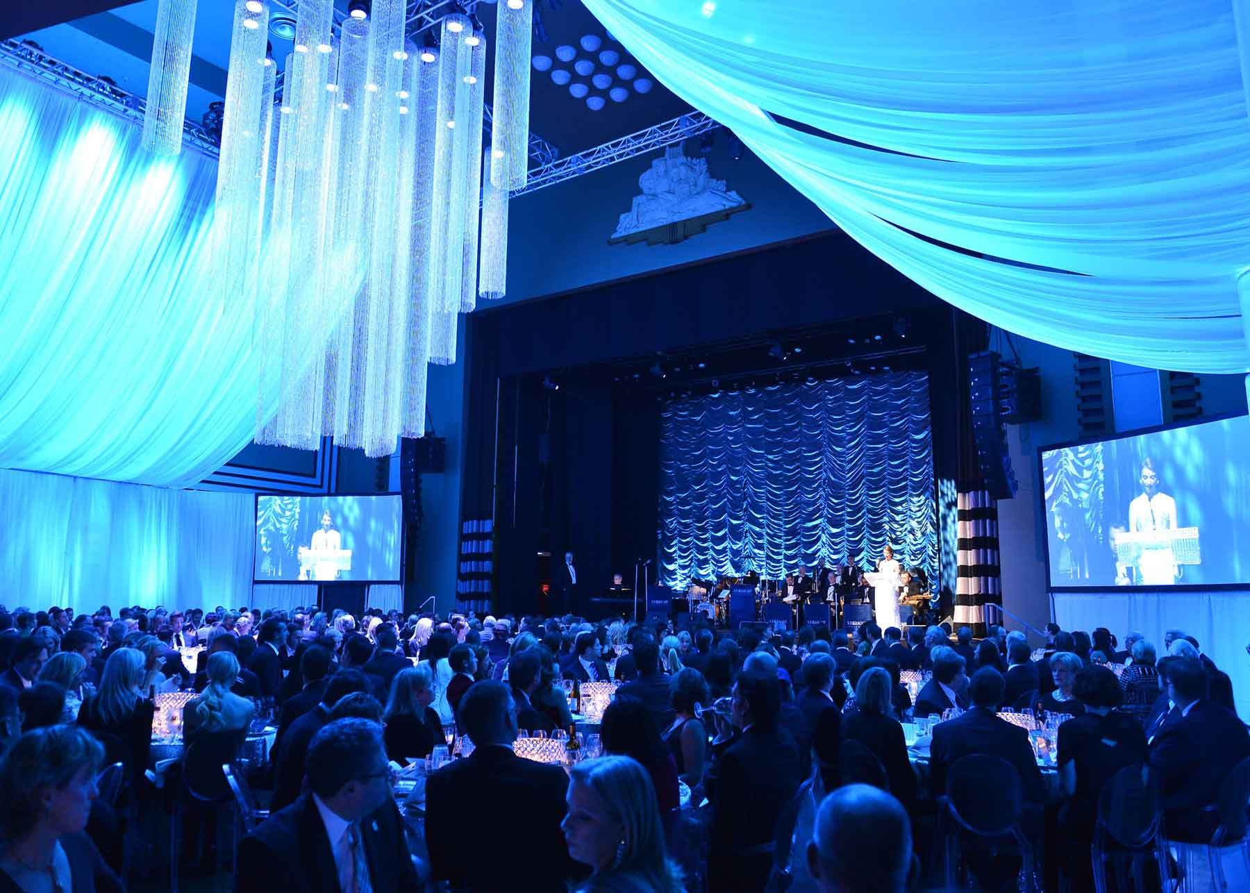 A crowd under atmospheric blue light at The Carlu event venue in Toronto watching a woman in a white dress reading on stage.