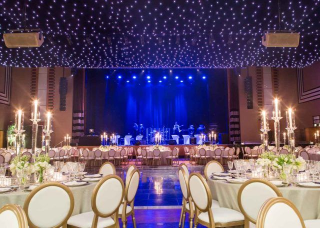 a large concert venue space with twinkling lights strung above a stage and a lot of luxury dining tables