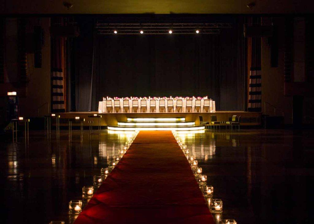 Candle-lit red carpet leading up to the stage in the Concert Hall at The Carlu