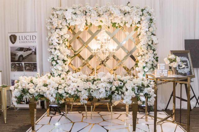 Glamorous floral archway and head table on display at the WedLuxe Wedding Show at The Carlu in Toronto