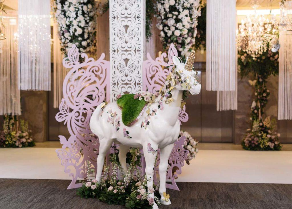 Unicorn statue decorated with flowers at the Toronto WedLuxe Wedding show at The Carlu