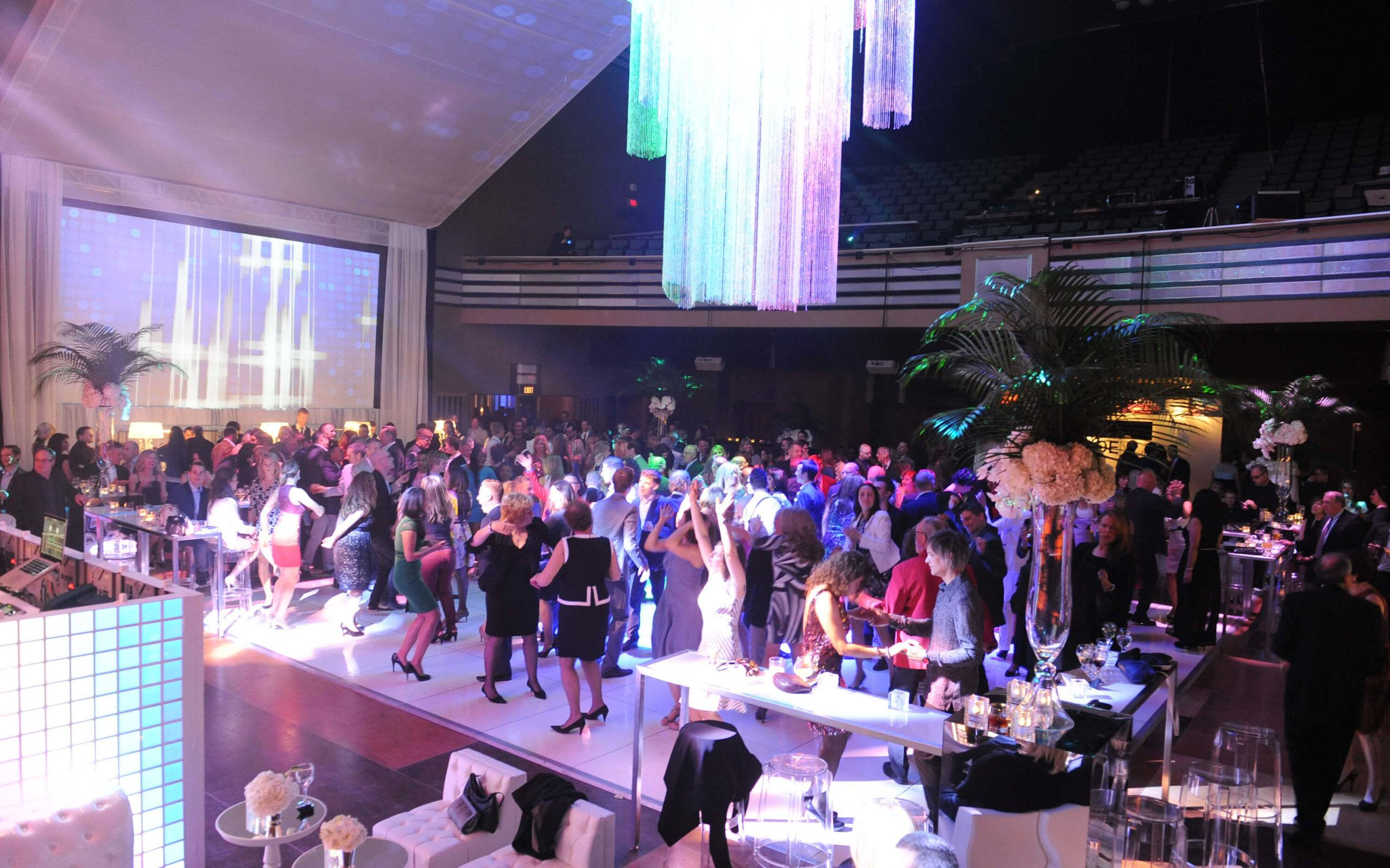 The Carlu anniversary party with a crowd of people dancing under the chandelier in the Concert Hall
