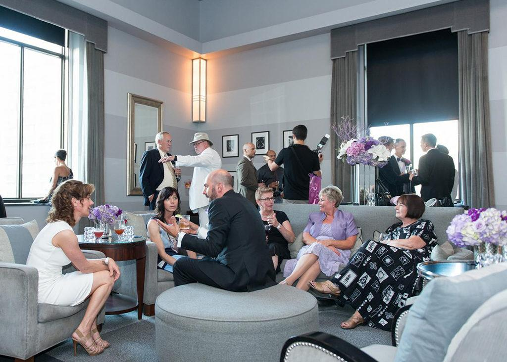 People conversing and mingling in the Clipper Room event space at The Carlu in Toronto