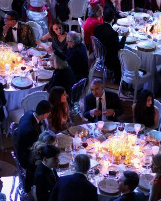 People dining around round table with lit candles in the Concert Hall of The Carlu