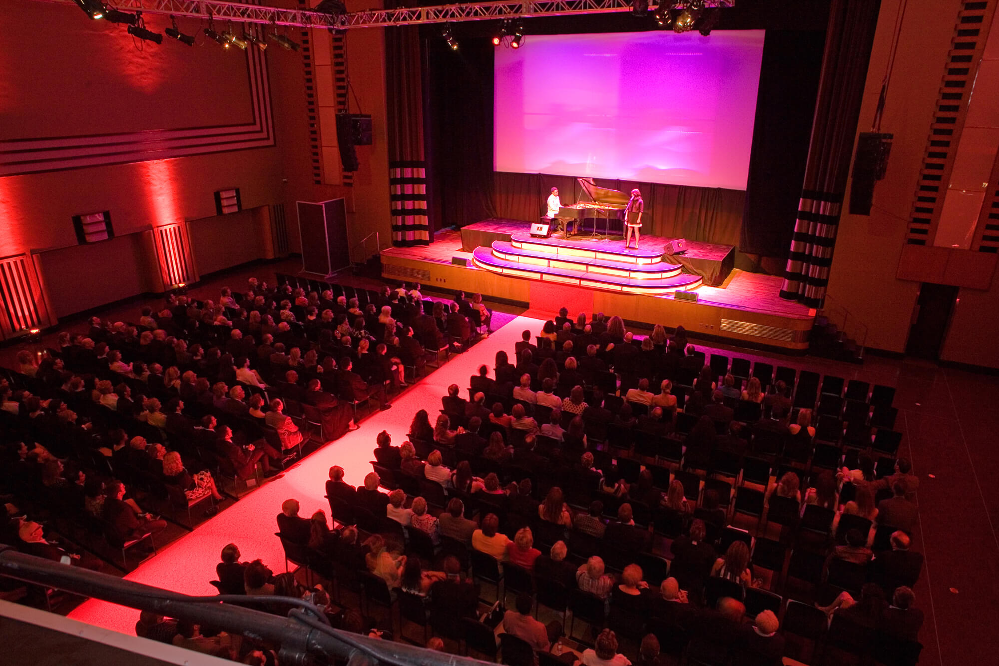 The Carlu Concert Hall filled with rows of guests facing a stage with a grand piano, pianist and woman on stage