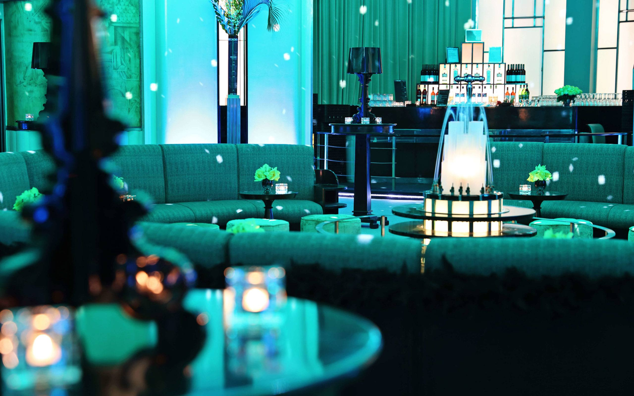 A detail shot of the fountain and seating in the Round Room at the Carlu. The room is lit with blue and green lighting.