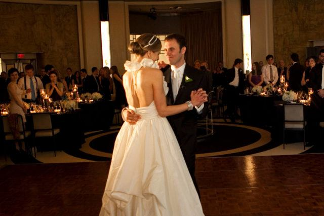 Bride and groom during their first dance with guests looking on in the Round Room at The Carlu