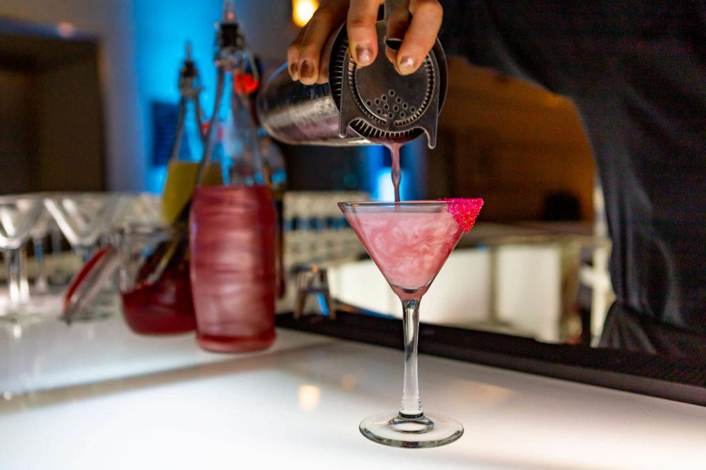 Shimmery cocktail being poured into a martini glass at The Carlu