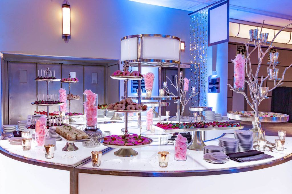 Dessert station with glittery, pink donuts, cupcakes, eclairs, cotton candy, and more