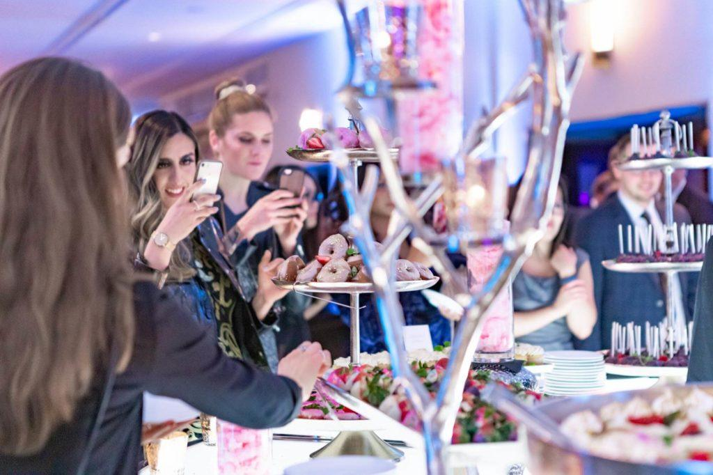 Guests taking photos of a dessert station at The Carly