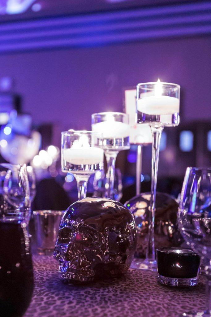 Candles and metallic skull table toppers at a gala event at The Carlu