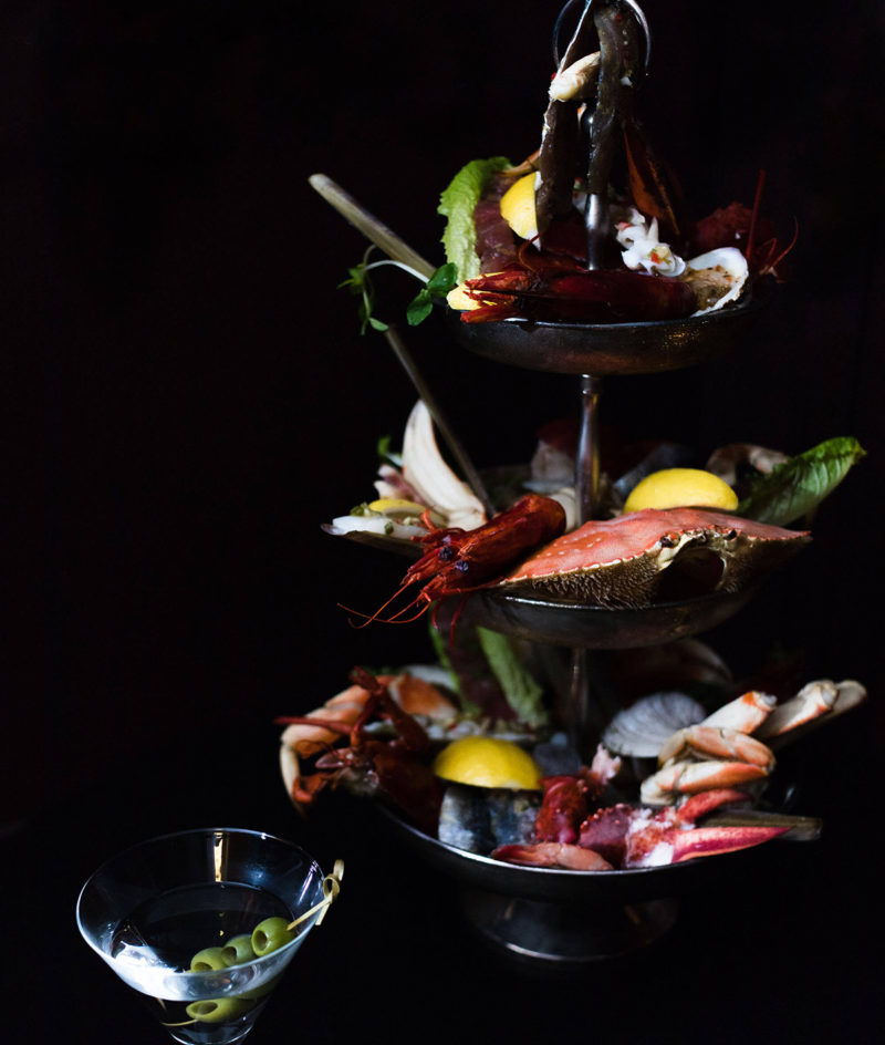 Seafood tower and martini against a dark black background