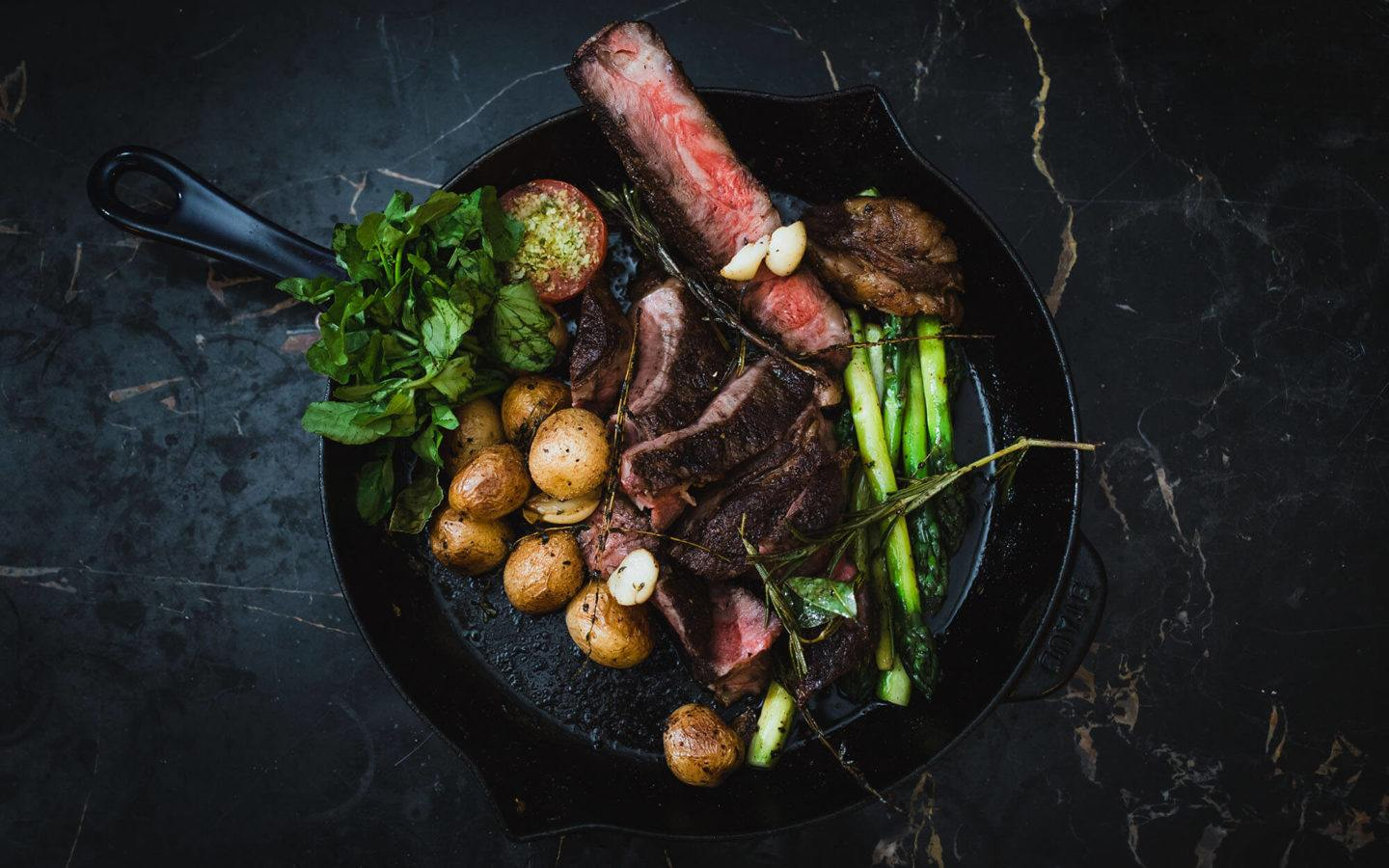 Cast iron pan filled with steak, potatoes and greens