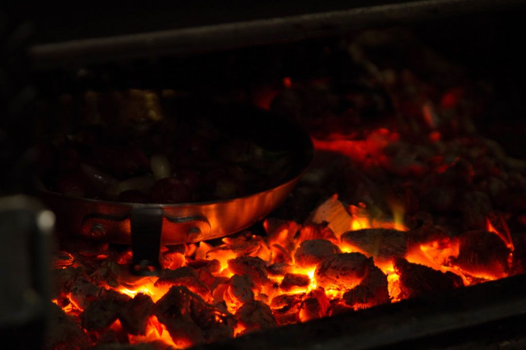 skillet sitting on a pile of hot coals
