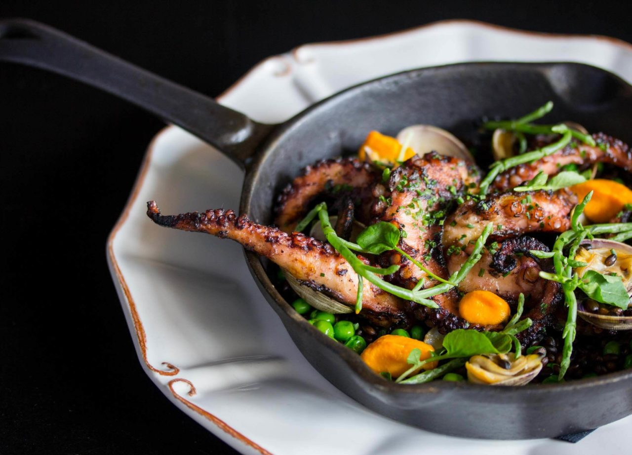 octopus in a cast iron skillet on a decorative plate