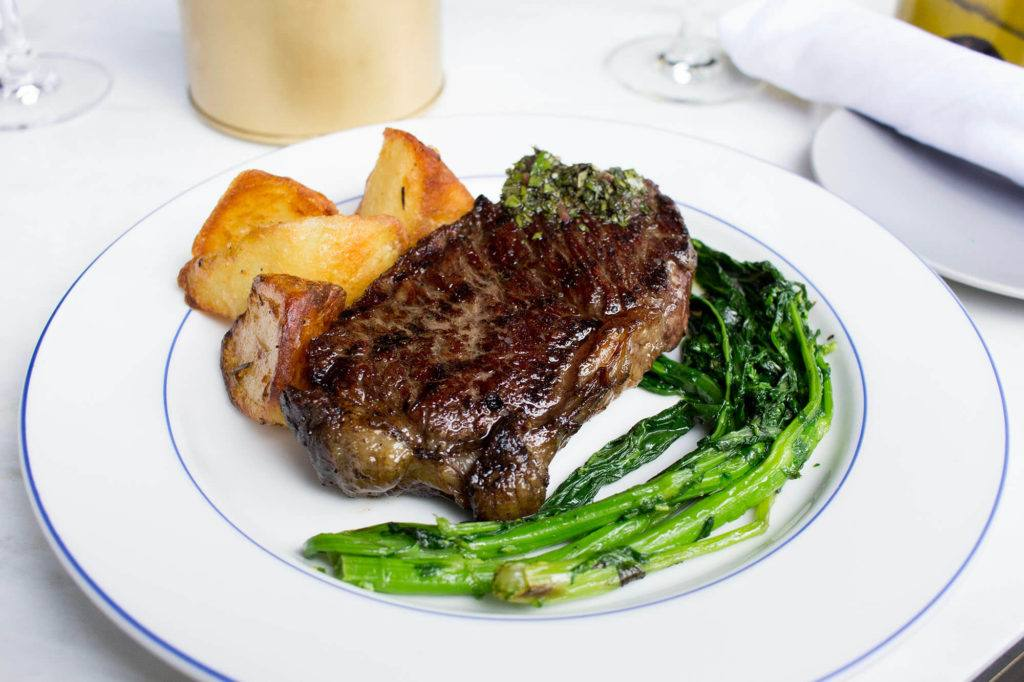 steak dish with potatoes and greens on white table