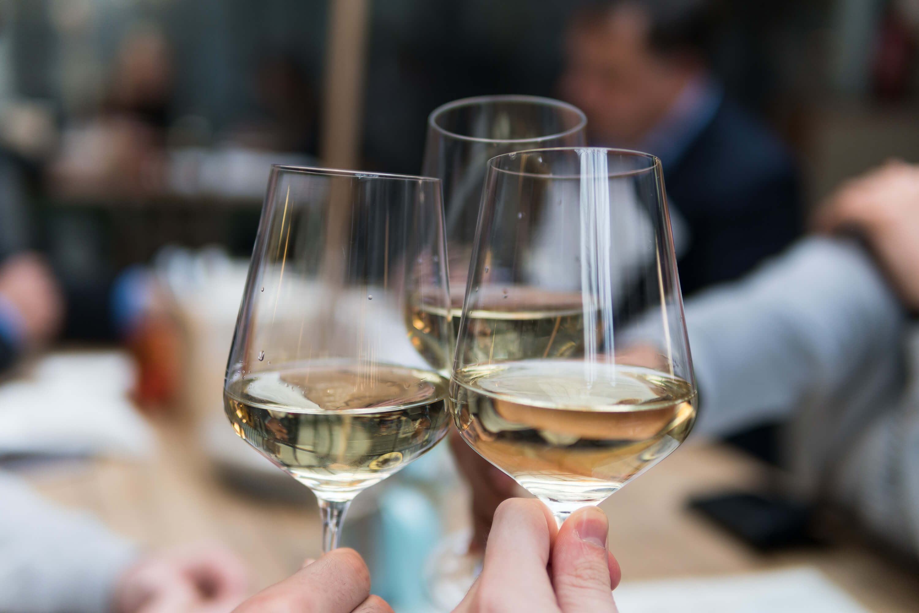 Three glasses of white wine clinking at Braven for daily drink specials