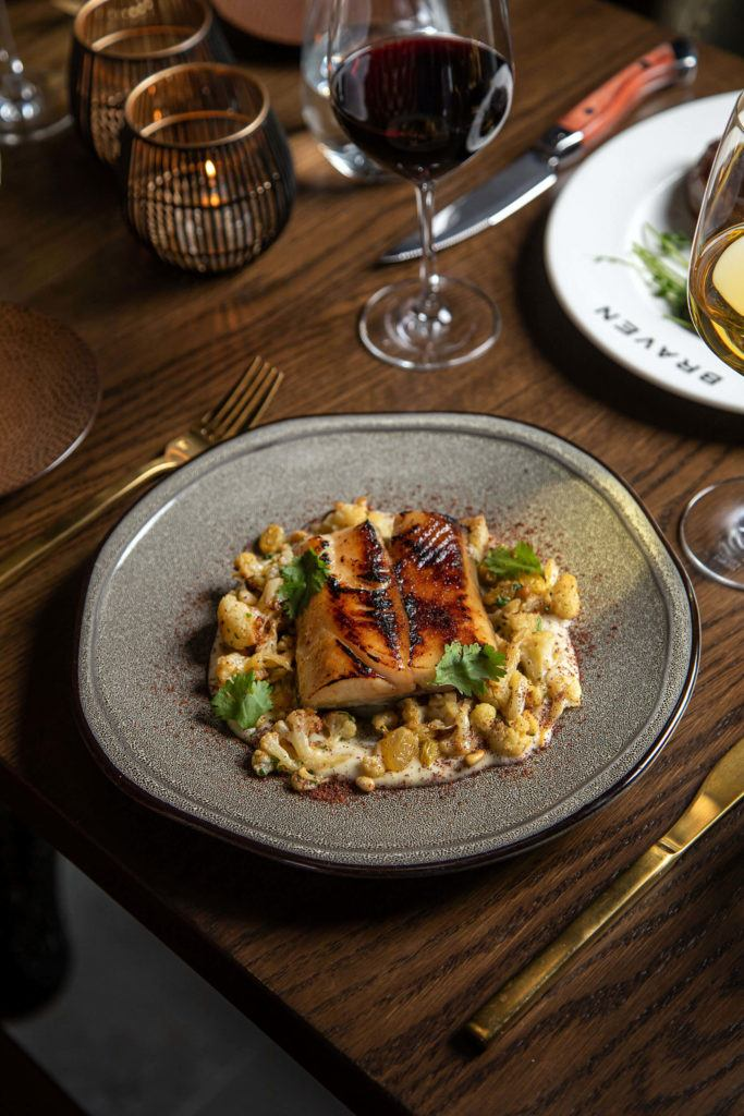 beautifully plated fish on grey plate