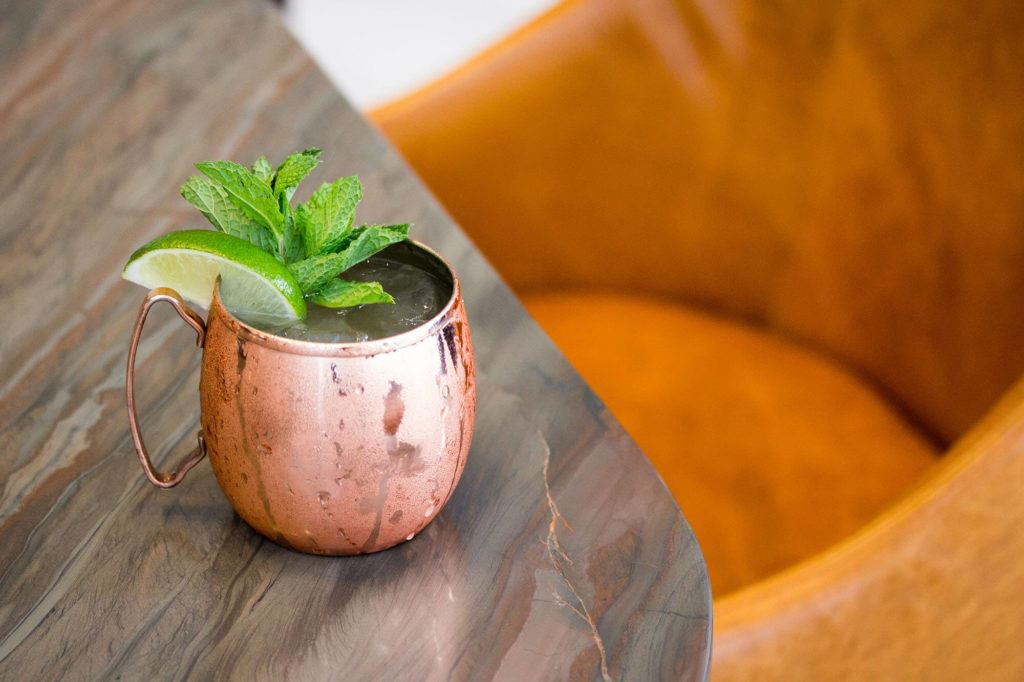 drink in copper cup garnished with lime and mint on marble surface