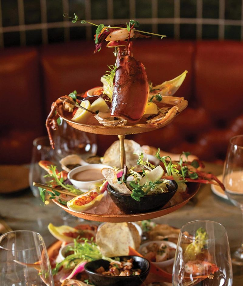 seafood on copper tower surrounded by wine glasses