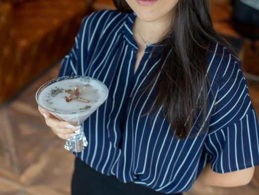 Woman with long dark hair holding a cocktail at Alchemy