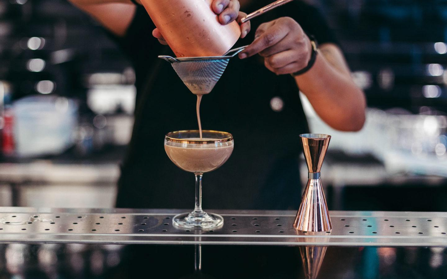 bartender straining cocktail into glass