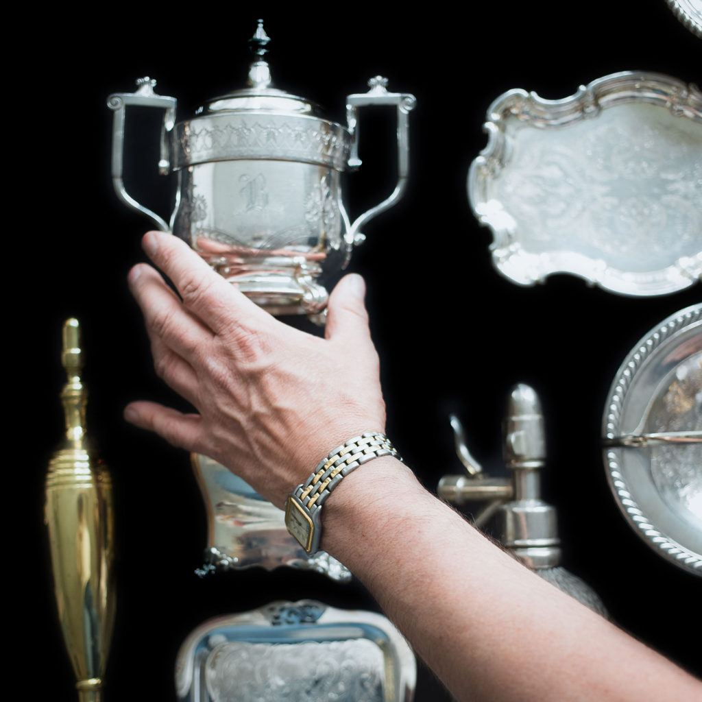 hand placing silver vessel on a surface