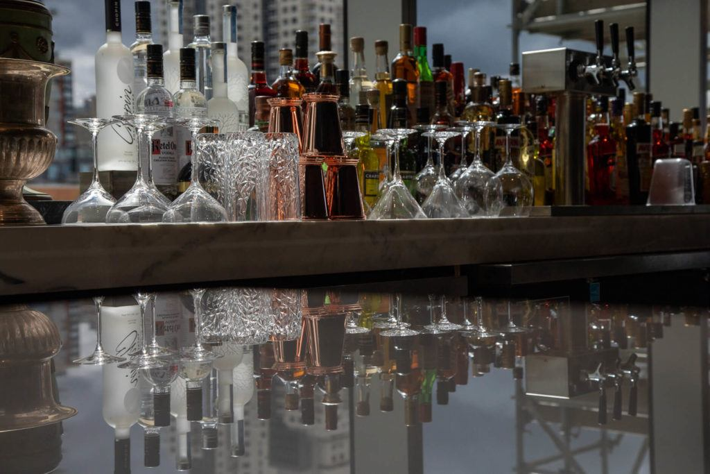 Liquor bottles and glassware at Alchemy cocktail bar in Edmonton
