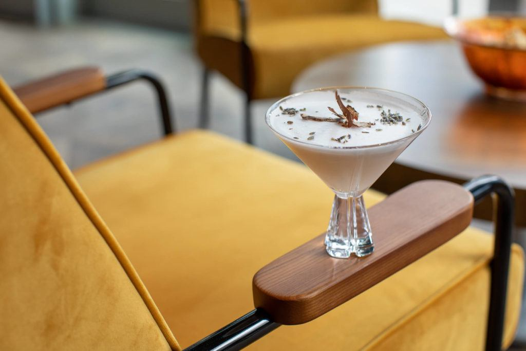 Cocktail in a martini glass on the arm of a yellow velvet chair
