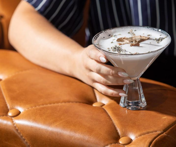 Hand holding a martini on the arm of a brown tufted leather chair