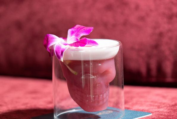 Dark pink cocktail in a skull-shaped glass, garnish with an orchid on a pink velvet background