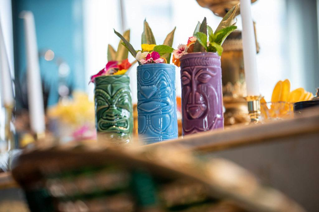 Three tiki cocktails garnished with pineapple leaves, mint and edible flowers