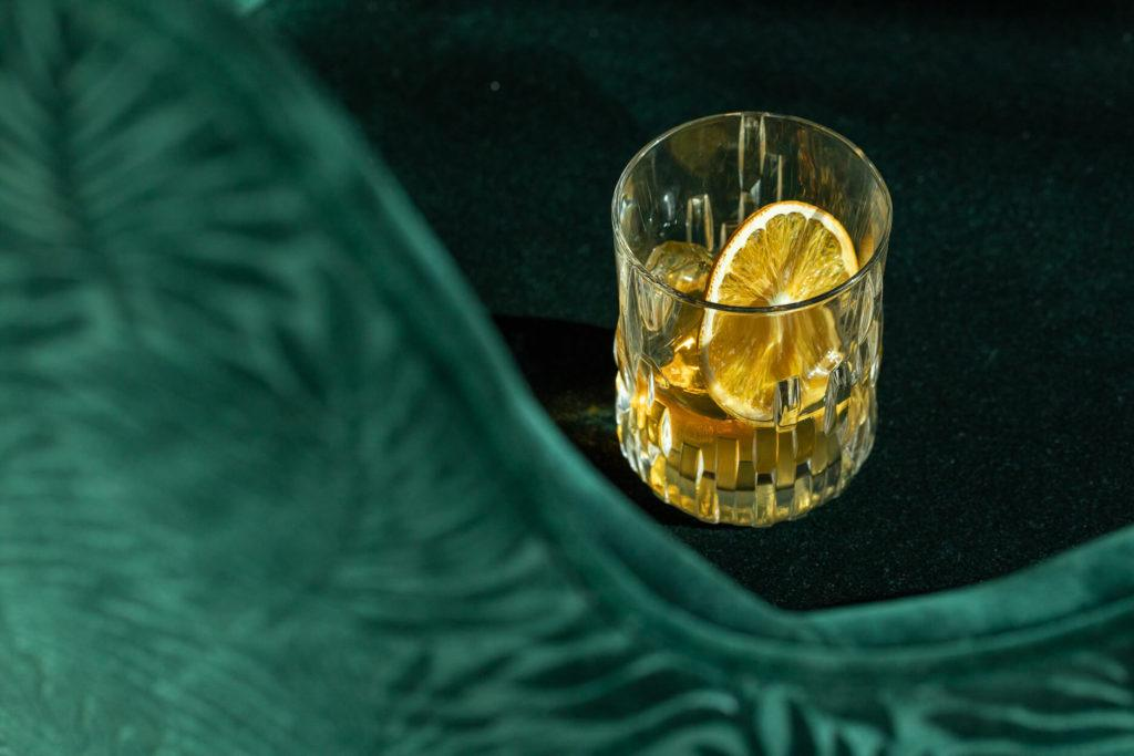 Cocktail served in a rocks glass and garnished with dried citrus, on a dark green velvet chair