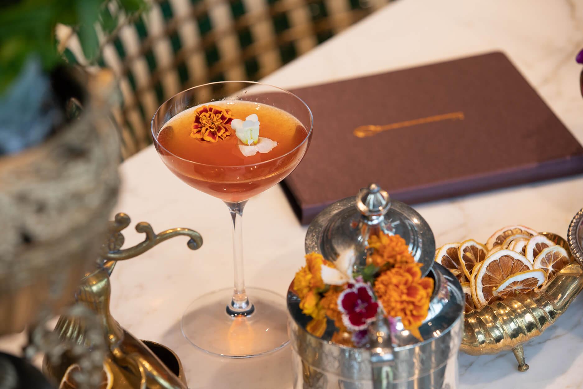 Dark orange cocktail garnished with edible flowers, sitting on the bar at Alchemy in Edmonton