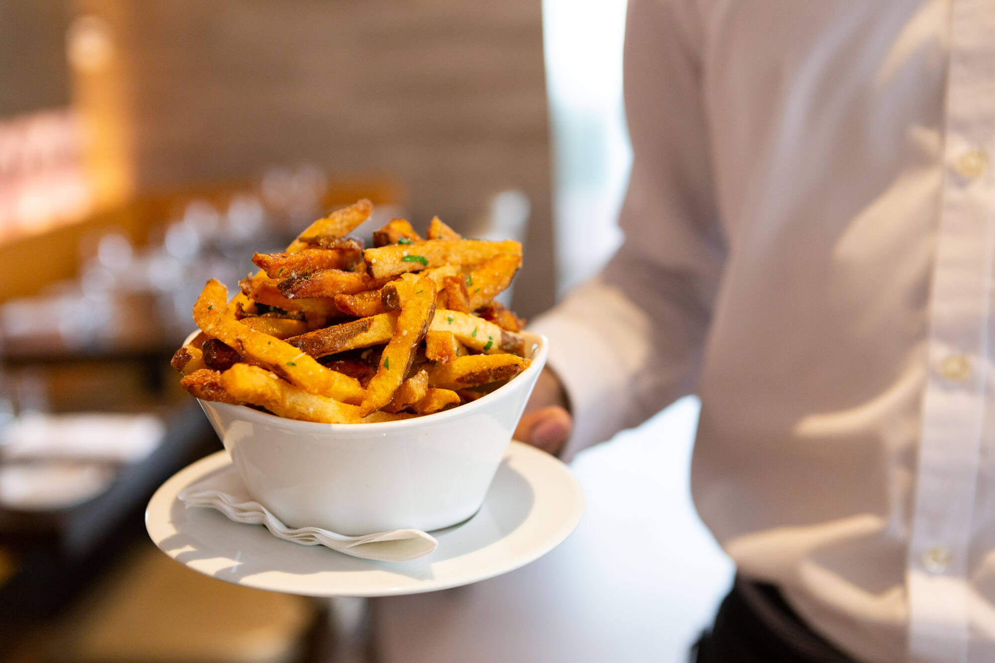 Server's torso holding out a bowl of french fries on a white ceramic dish