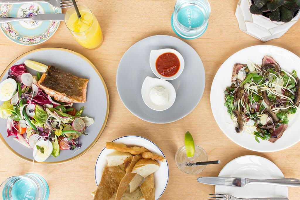 A spread on a wooden table at Kindred including the Salmon Nicoise Salad and the Alberta Beef Carpaccio, with condiments and other cutlery surrounding.