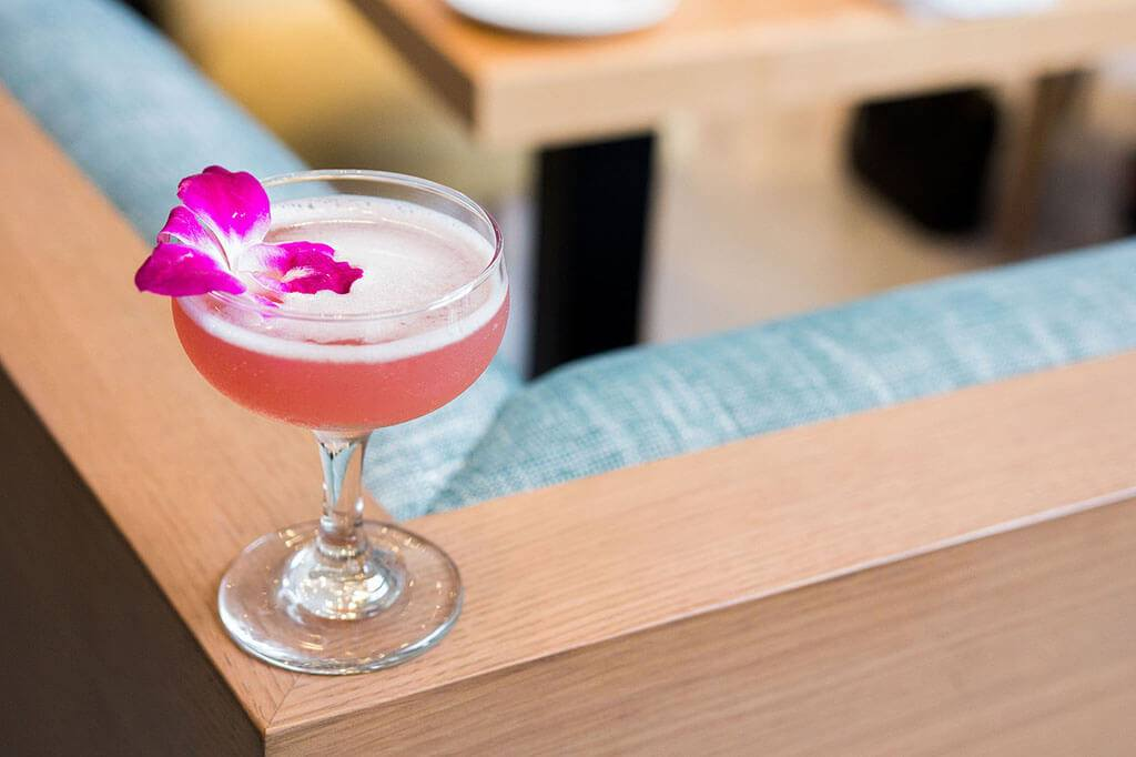 "Kindred's ""The Florist"" cocktail sitting on a bench seat. A pink drink dressed with a pink and white flower."