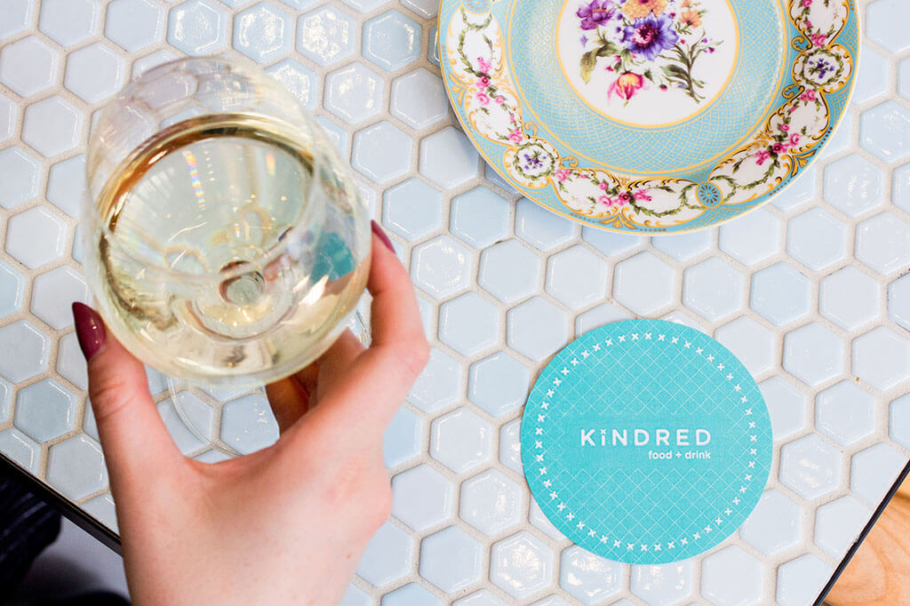 A glass of white wine with a hand around it, sitting on a coaster with another Kindred branded coaster next to it and a blue dish in the background.
